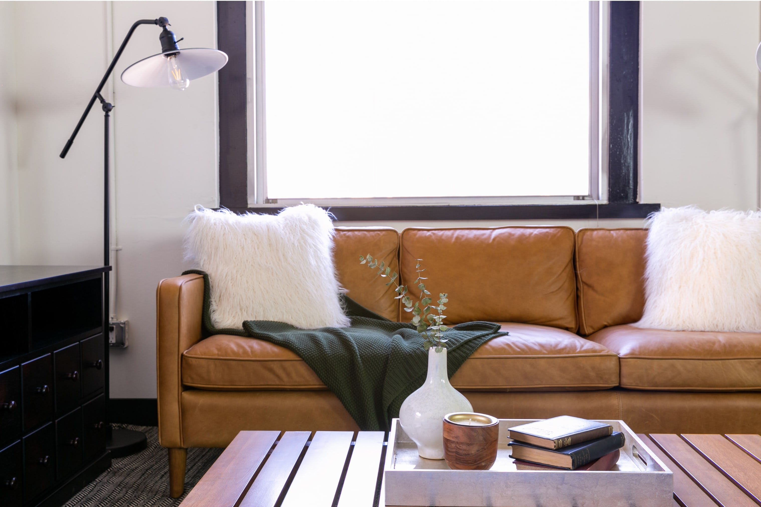 Leather couch with fluffy pillows.