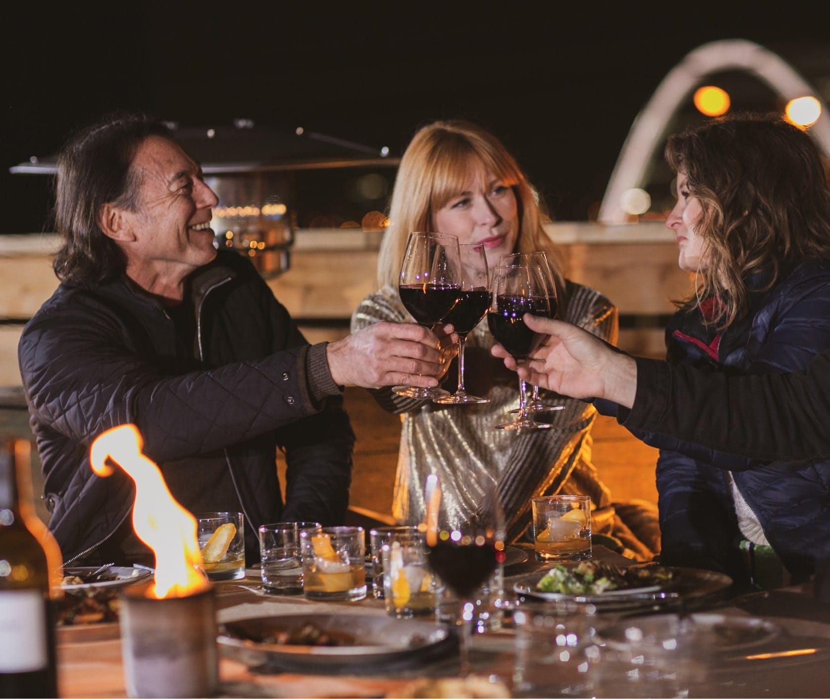 Three people clinking wine glasses.